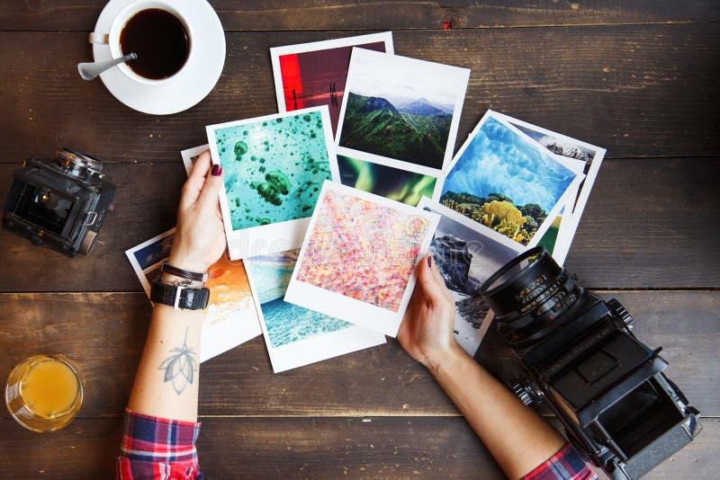 La vista superiore del ` s delle donne passa le foto stampate tenuta immagini stock