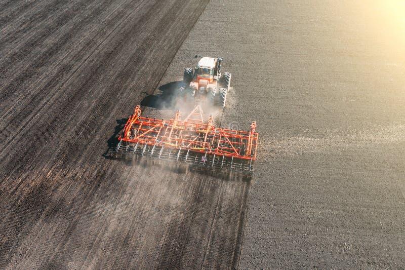 La vista superiore del trattore industriale agricolo ara il campo del suolo per la semina, vista aerea Coltivazione della terra fotografia stock libera da diritti