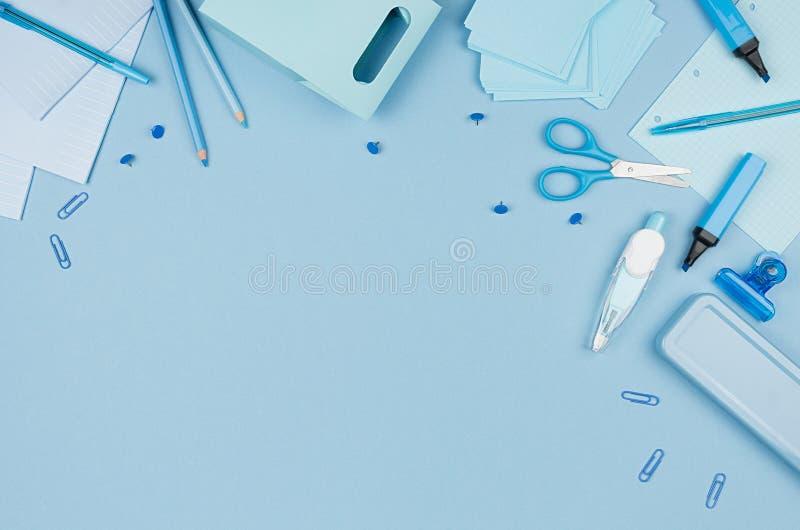 La vista superiore della cancelleria blu della scuola come decorativa rasenta il fondo pastello molle, la vista superiore, orizzo immagine stock