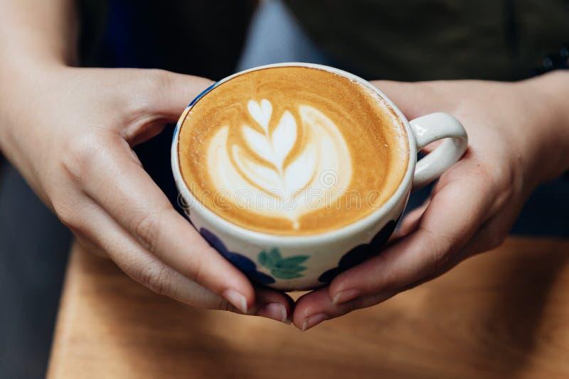 La vista superiore delle mani che tengono una forma del cuore di arte del Latte è servito in tazza ceramica sulla tavola di legno immagini stock