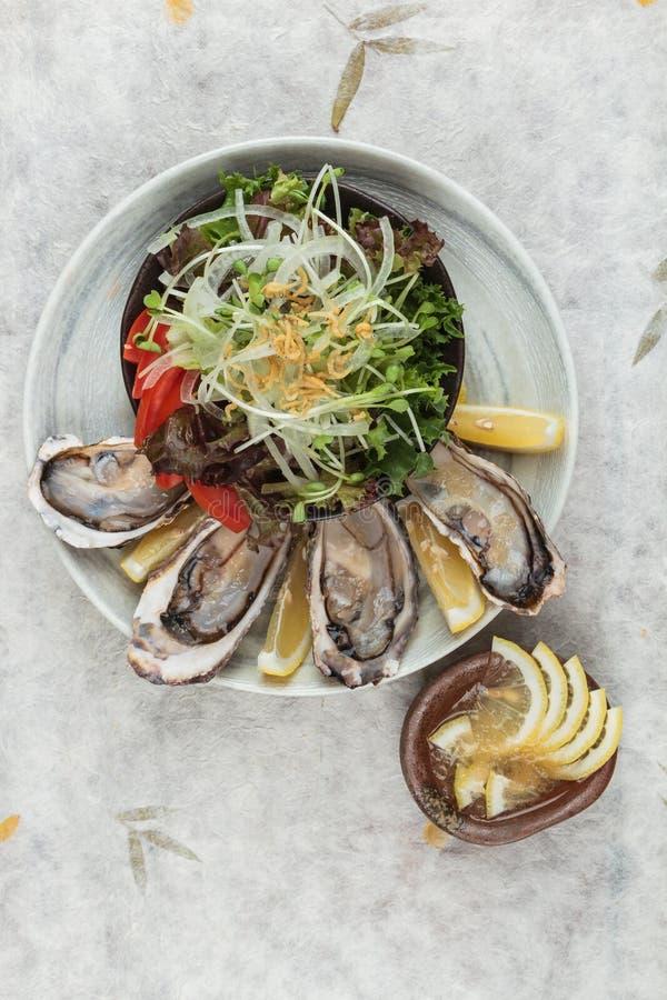 La vista superiore delle ostriche fresche e dell'insalata giapponese è servito con la salsa del limone ed affettato sulla ciotola fotografia stock
