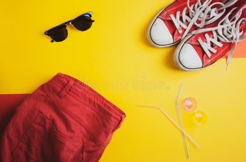La vista superiore delle scarpe da tennis rosse, rossa mette ed occhiali da sole su fondo giallo fotografia stock libera da diritti