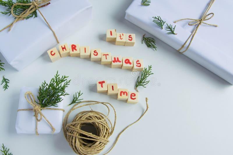 """La vista superiore di bianco handcraft i contenitori di regalo con """"è le lettere di legno del testo di tempo di Chrismas """"ed i ra fotografie stock libere da diritti"""