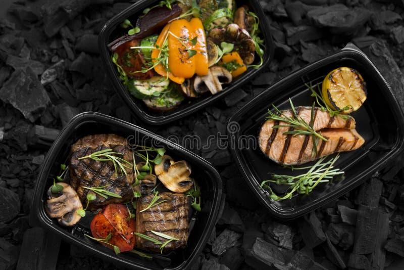 La vista superiore di carbone ha cucinato l'alimento sano dentro porta via le scatole fotografia stock