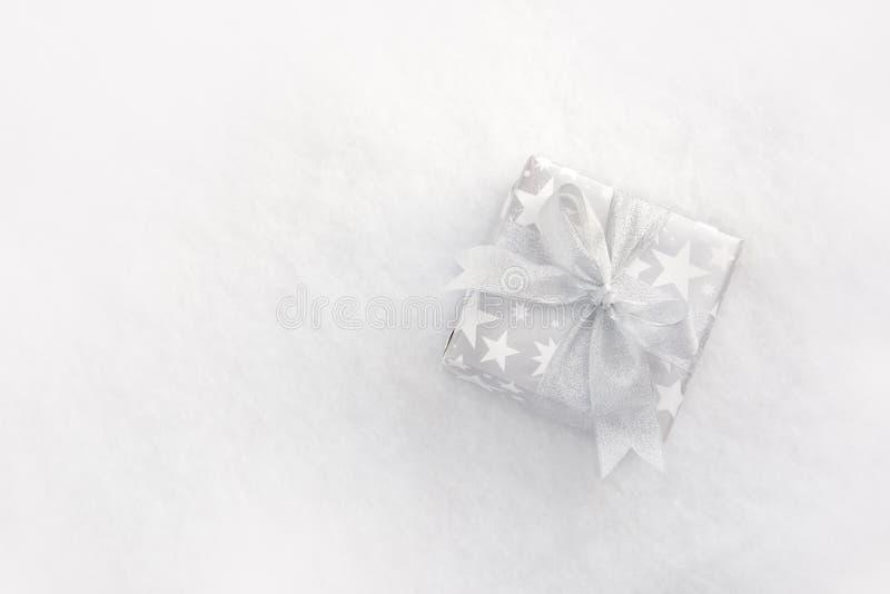 La vista superiore di un contenitore di regalo di natale nello spostamento d'argento nasconde un fondo lanuginoso bianco fotografia stock