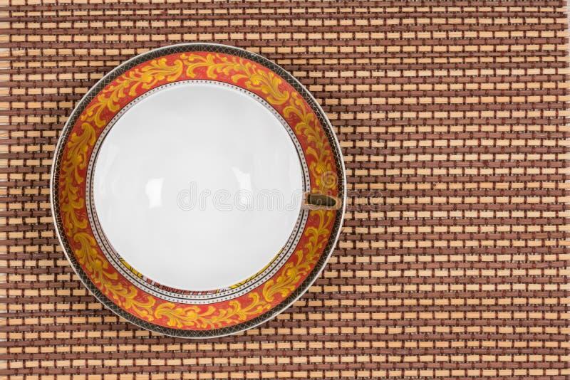 La vista superiore di uno stile orientale vuoto ha dipinto il tazza da the su un piattino situato su una stuoia di bambù di legno immagine stock libera da diritti