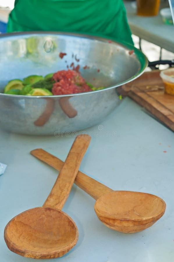 La vista superiore, distanza media all'artigiano ha scolpito il cucchiaio di legno davanti ad una ciotola del metallo di ingredie immagine stock