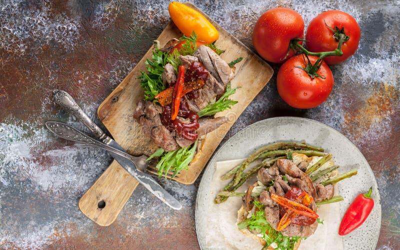 La vista superiore ha grigliato il panino con carne di tacchino, asparago fritto, i funghi, i peperoni, i pomodori ed i verdi fotografia stock libera da diritti