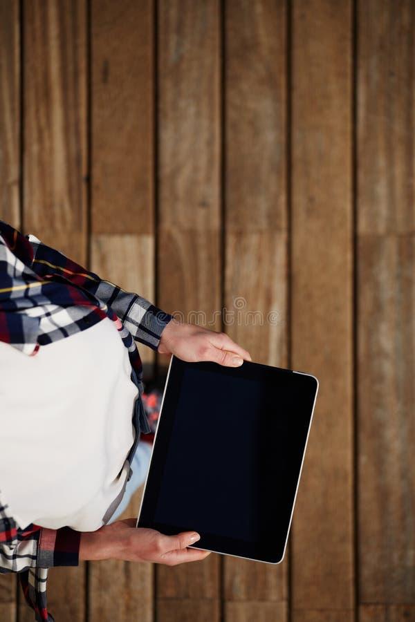 La vista superiore ha sparato di una donna che tiene la compressa digitale con un primo piano dello schermo in bianco fotografie stock