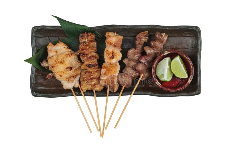 La vista superiore isolata degli spiedi arrostiti stile giapponese del pollo di Yakitori con il pollo e l'organo interno è servit fotografie stock
