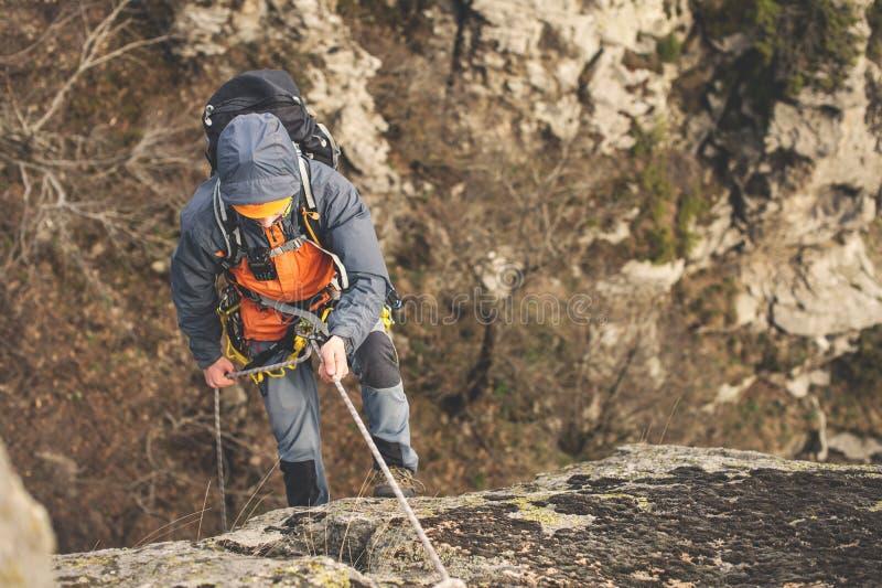 La vista superiore, lo scalatore sulla corda ed il casco aumenta su roccia verticale fotografia stock