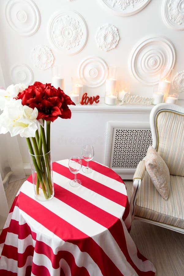 La vista superiore su un rosso ha spogliato la tavola con i fiori di contrapposizione freschi e luminosi in un vaso di vetro fotografia stock