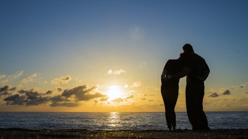 La vista trasera de un par siluetea el sol de abrazo y de observación en la playa fotos de archivo libres de regalías
