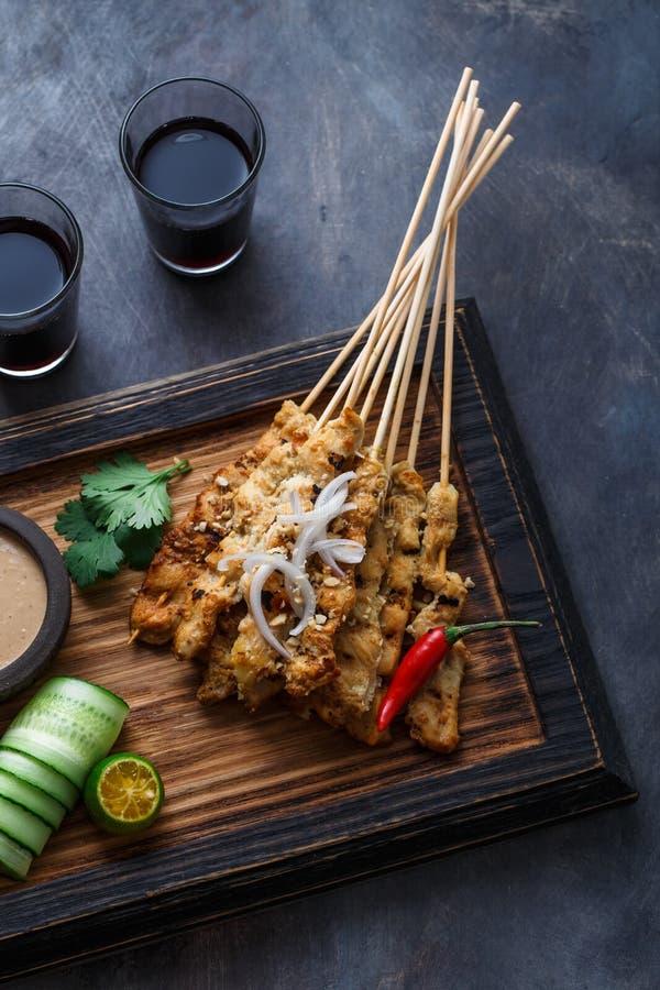 La vista vicina degli spiedi malesi del pollo - satay o sazia il ayam con la salsa dell'arachide, fondo scuro fotografie stock libere da diritti