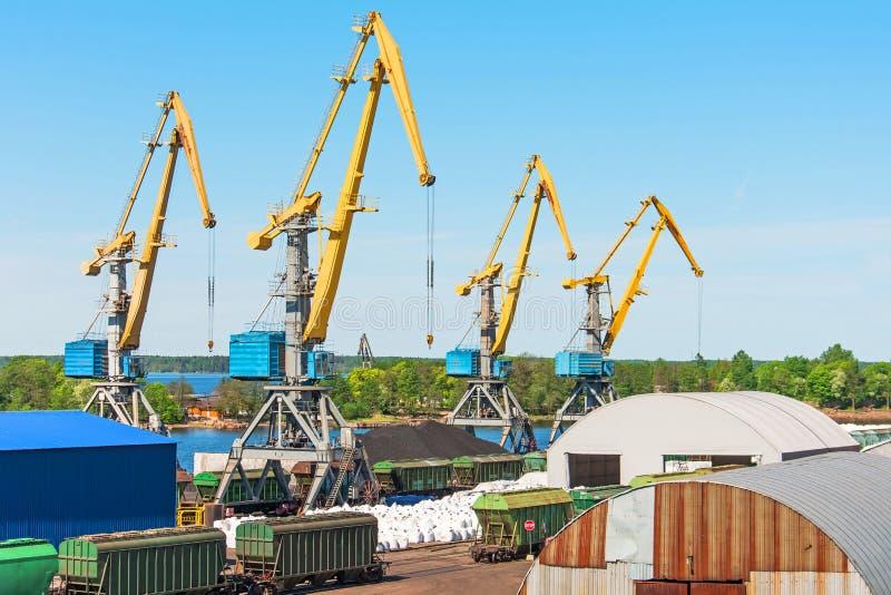 La visualizzazione della porta del carico, con l'alto mare cranes per le merci ed il carico di carico alle navi dal pilastro dell immagini stock libere da diritti