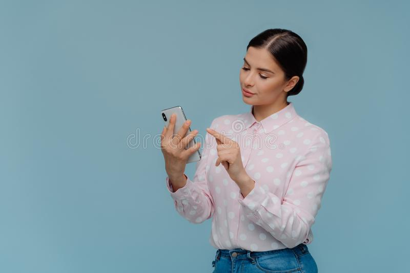 La vita su ha sparato della bruna in abbigliamento elegante, telefono cellulare di usi, concentrato in schermo, sceglie la nuova  fotografie stock libere da diritti