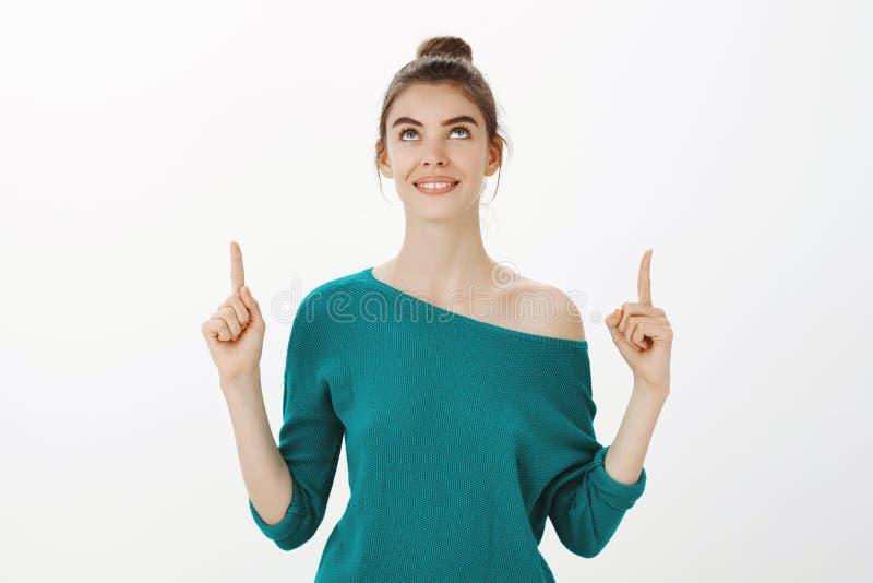 La vita-su ha sparato della femmina europea sveglia femminile in maglione sciolto verde, guardando ed indicando su con il sorriso fotografia stock libera da diritti