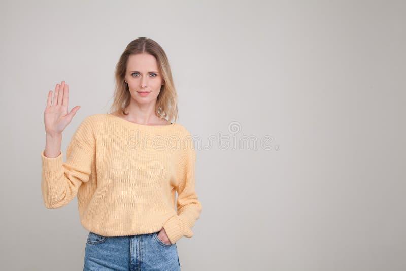 La vita sul ritratto va giovane donna bionda con emozione calma che mostra la sua palma della mano alla macchina fotografica, un' immagine stock