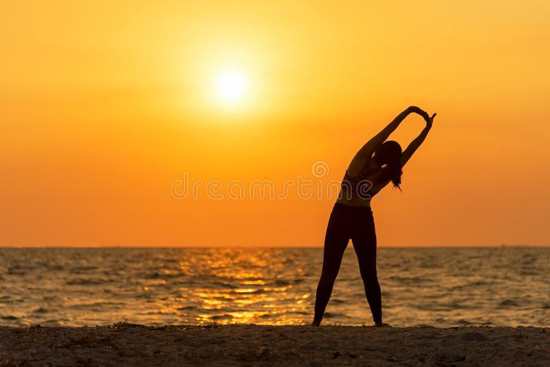 La vitalité de paix de femme d'esprit de mode de vie d'esprit d'exercice, extérieur de silhouette sur le lever de soleil de mer,  photographie stock libre de droits