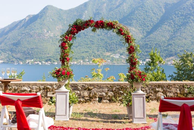 La voûte a décoré des fleurs rouges fraîches pour une cérémonie l'épousant photos stock