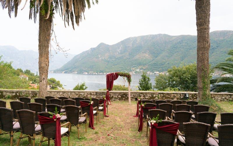 La voûte et les chaises ont décoré des fleurs fraîches dans des tons rouge foncé pour la cérémonie l'épousant images libres de droits