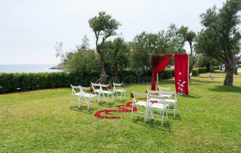 La voûte et les chaises ont décoré des fleurs fraîches dans des tons rouges pour la cérémonie l'épousant sur la pelouse verte image stock