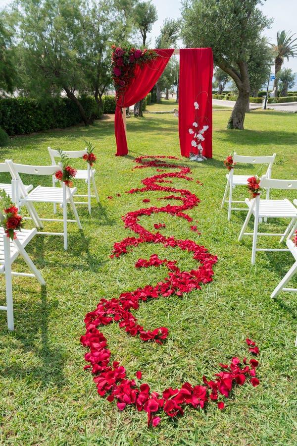 La voûte et les chaises ont décoré des fleurs fraîches dans des tons rouges pour la cérémonie l'épousant sur la pelouse verte image libre de droits