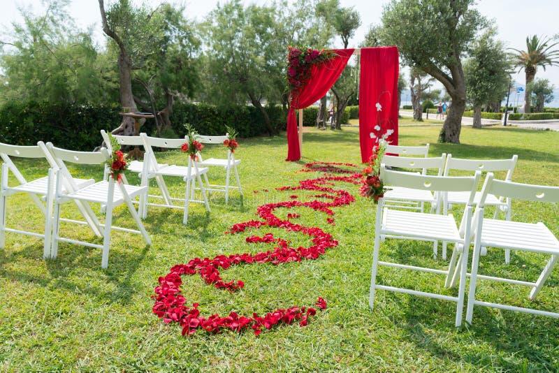 La voûte et les chaises ont décoré des fleurs fraîches dans des tons rouges pour la cérémonie l'épousant sur la pelouse verte images stock
