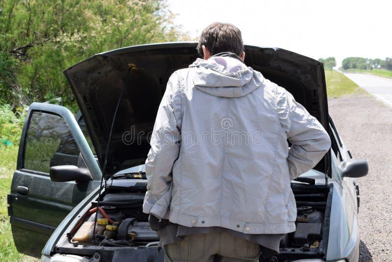 La voiture étée en panne sur la route et un homme regarde ce qui s'est cassée, une voiture cassée avec un capot ouvert se tient s images stock