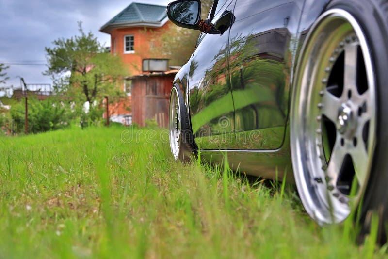 La voiture accordée noire est garée dans la cour près d'une maison privée Roues faites sur commande, jantes polonaises photo libre de droits