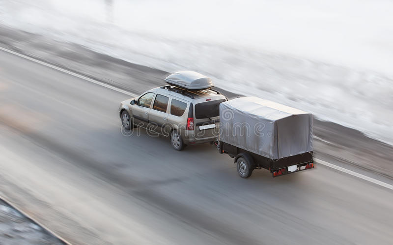 La voiture avec la remorque monte sur la route d'hiver images libres de droits