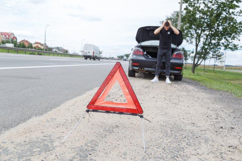 La voiture avec une panne à côté de la route, homme place la triangle d'avertissement photos libres de droits