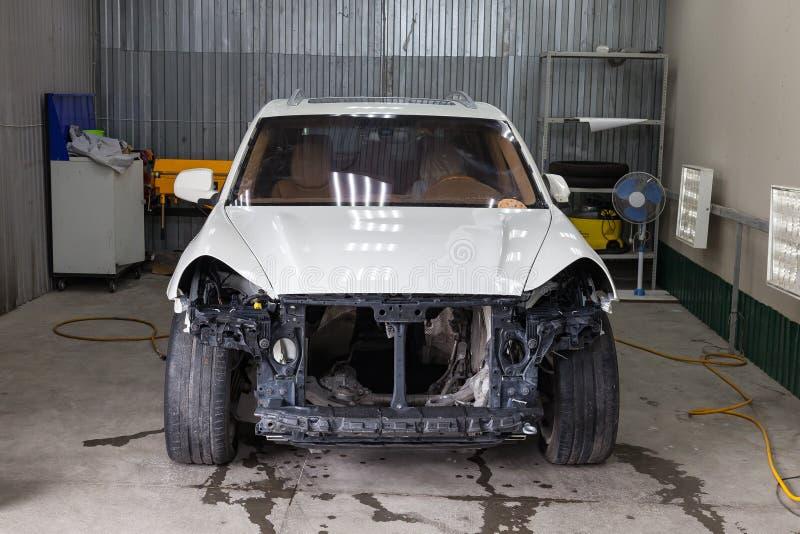 La voiture blanche dans le corps du souv se prépare à peindre le corps sans phares et pare-chocs dans un atelier de réparation photos stock