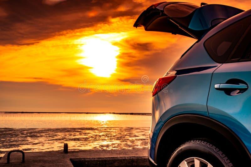 La voiture compacte bleue de SUV avec le sport et la conception moderne s'est garée sur la route bétonnée par la mer au coucher d photo stock