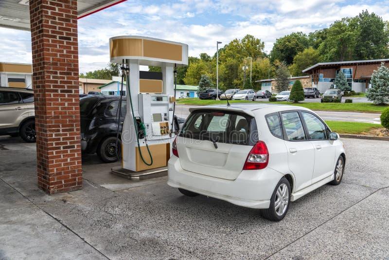 La voiture compacte générique achète l'essence à l'épicerie générique image stock