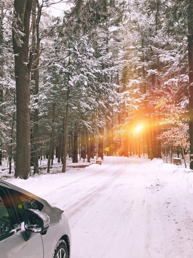 La voiture conduit sur une route de traînée couverte de neige photos libres de droits