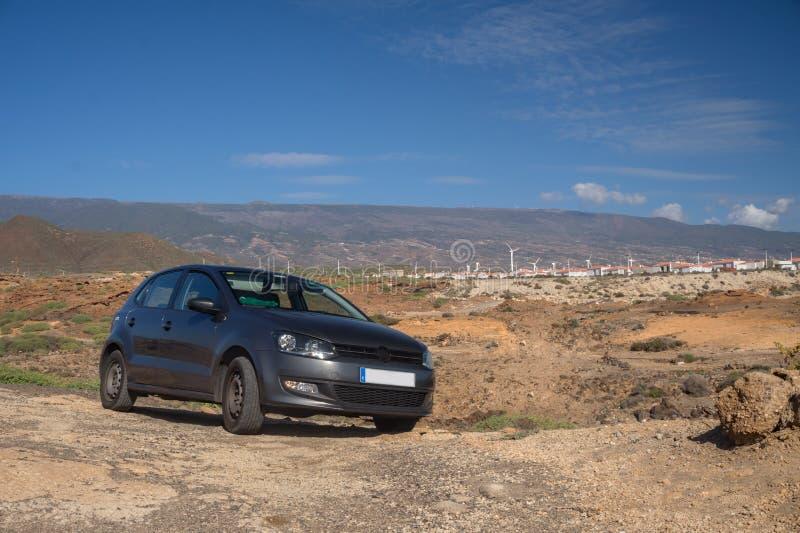 La voiture dans le désert à l'arrière-plan des montagnes avec des moulins à vent Transport sur l'île de Ténérife photo libre de droits