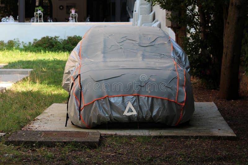 La voiture de berline de famille est partie dans l'arrière-cour sur l'ardoise concrète couverte de dispositif de couverture gris  photographie stock