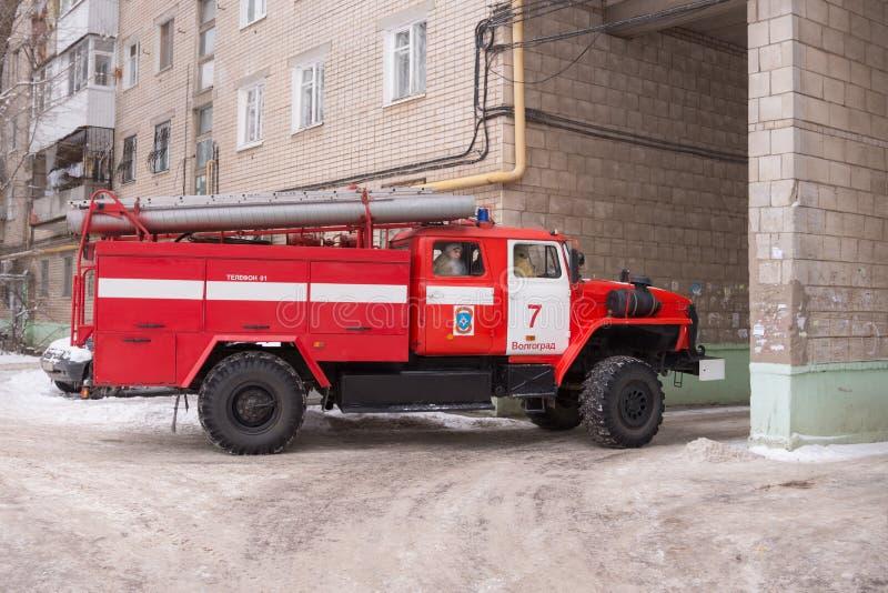 La voiture de pompiers part de la cour d'un bâtiment à plusiers étages après l'appel image stock