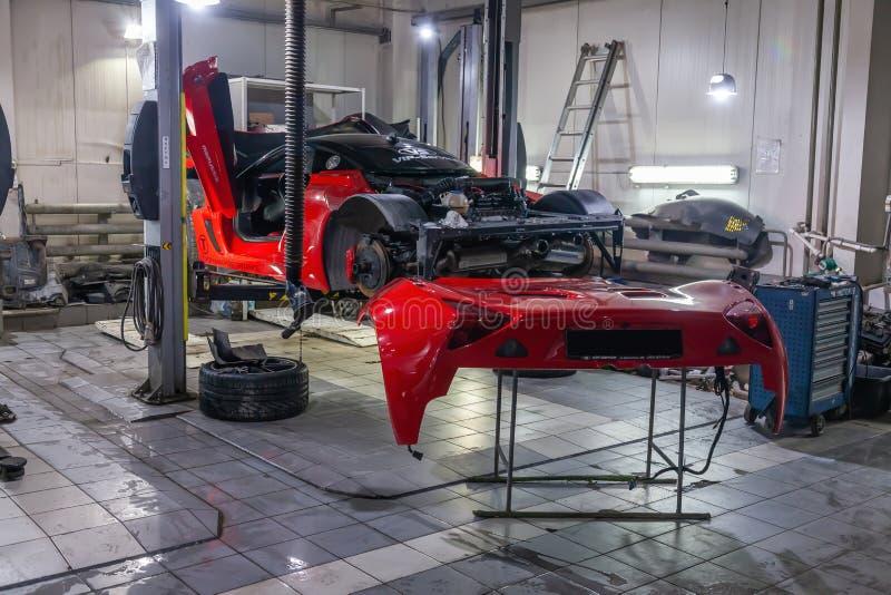 La voiture de sport très chère et puissante de couleur rouge, démontée pour la réparation, soulevée sur un ascenseur dans le serv photographie stock libre de droits