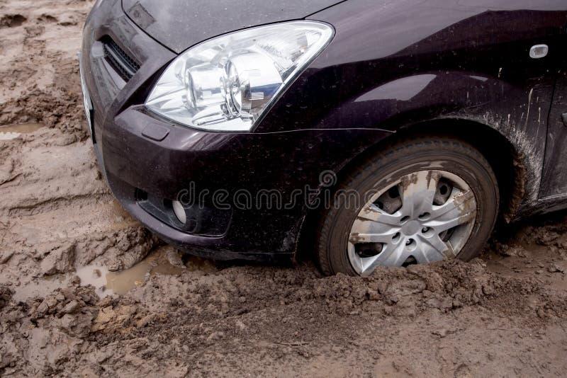la voiture est coincée sur une mauvaise route dans la boue images libres de droits