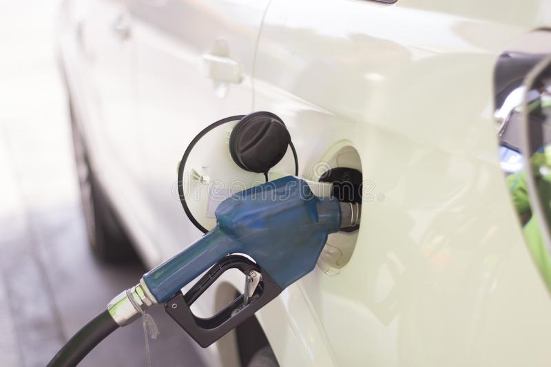 La voiture est remplie de combustible avec l'essence à une station service photos libres de droits