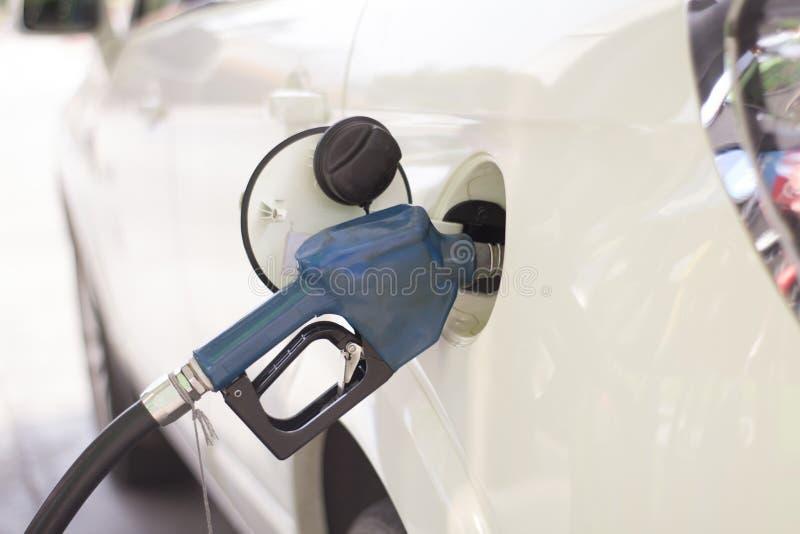 La voiture est remplie de combustible avec l'essence à une station service photographie stock libre de droits