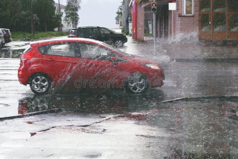 La voiture mobile pulvérise un magma quand la forte pluie se laisse tomber photographie stock libre de droits