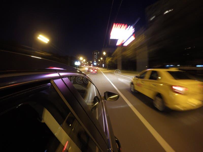 La voiture se déplace à la grande vitesse sur la route de nuit dans la ville image libre de droits