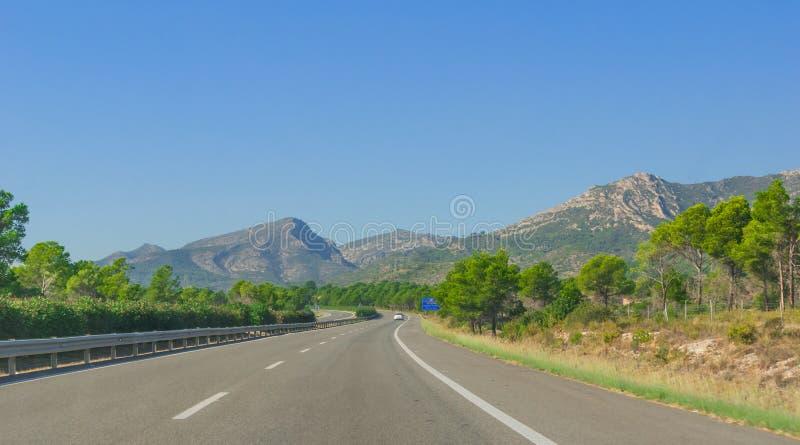 La voiture solitaire descend la route par les collines et les montagnes côtières de l'Espagne rurale photo stock