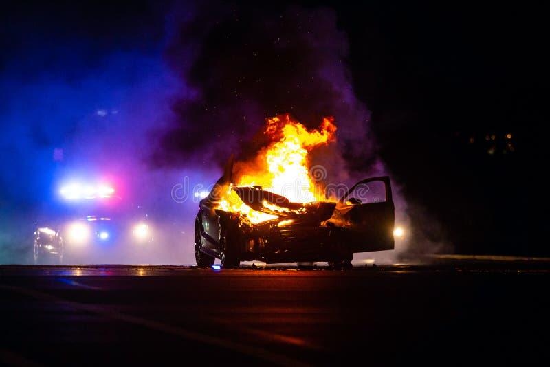 La voiture sur le feu la nuit avec la police s'allume à l'arrière-plan photos stock
