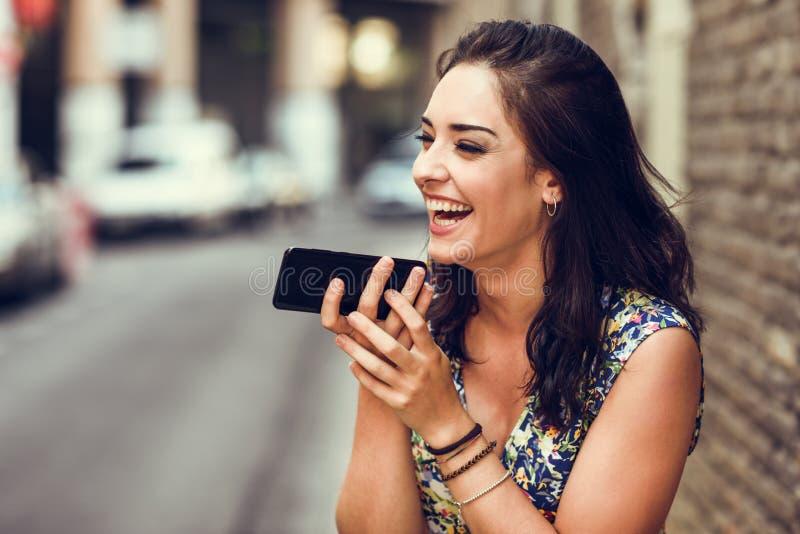 La voix de sourire d'enregistrement de jeune femme notent dans son téléphone intelligent photos libres de droits