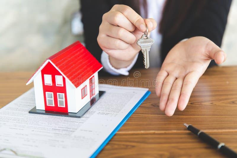 La vostra nuova casa, chiave della casa della tenuta dell'agente immobiliare al suo cliente dopo la firma dell'accordo di contrat fotografie stock libere da diritti
