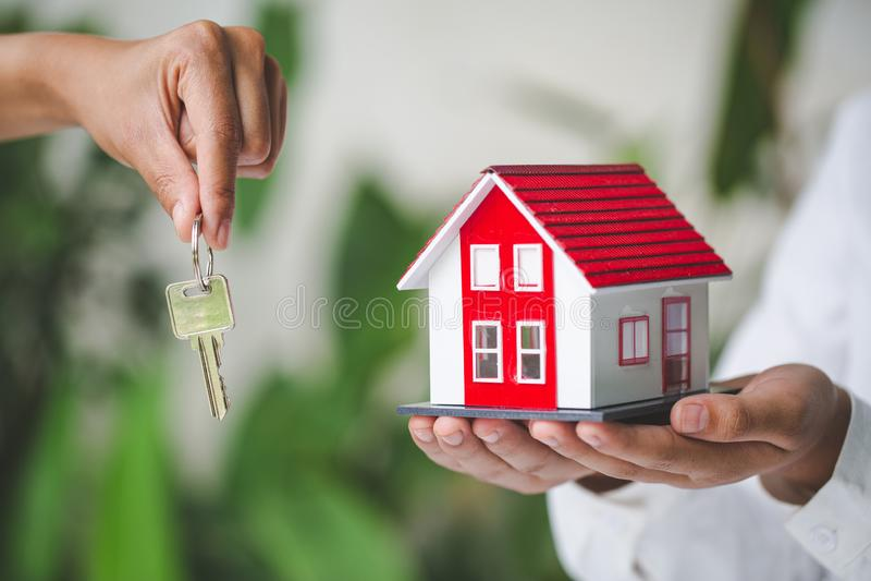 La vostra nuova casa, chiave della casa della tenuta dell'agente immobiliare al suo cliente dopo la firma dell'accordo di contrat fotografia stock libera da diritti